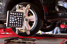 Close up image of a black car on an automotive alignment systems