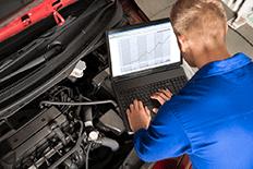 Man using automotive diagnostic equipment to analyze a problem with a car