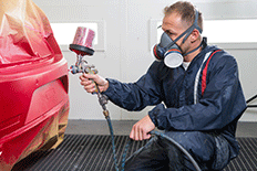 Man in a painting mask and protective clothing spray painting a piece of equipment