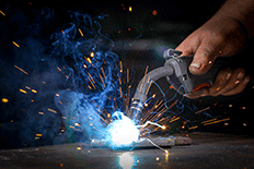 Close up image of a man using welding equipment