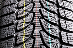 Close up image of tire treads with three vertical lines which are yellow, red, and blue