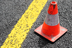 Orange and white traffic cone next to a yellow line on a road
