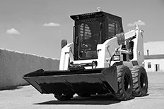 Black and white image of a skid loader in a lot