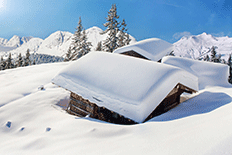 Color image of snowed-in cabins with mountains and pines in the background