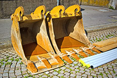 Two yellow excavator buckets on a cobblestone street next to building materials