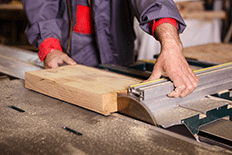 Color image of a man using a woodworking table saw